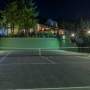 'The tennis court overlooked by its own gazebo  floodlit in the evening